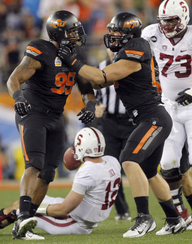 Photo - Oklahoma State's Richetti Jones (99) and Cooper Bassett (80) celebrate a sack Jones' sack on Stanford's Andrew Luck (12) during the Fiesta Bowl between the Oklahoma State University Cowboys (OSU) and the Stanford Cardinal at the University of Phoenix Stadium in Glendale, Ariz., Monday, Jan. 2, 2012. Photo by Sarah Phipps, The Oklahoman