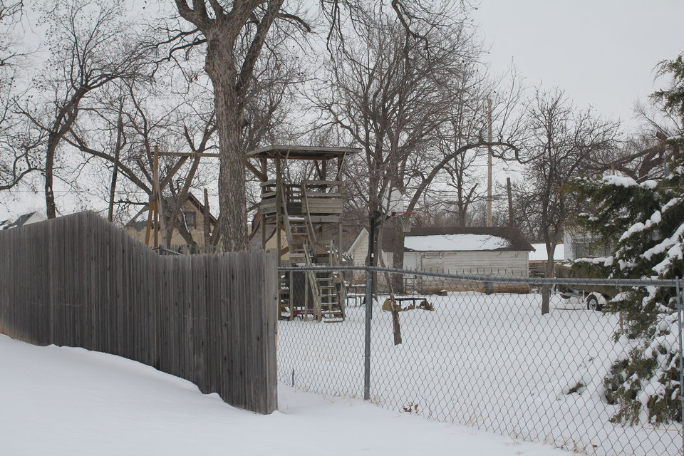 Photo - Shown in this photo is the backyard of Uwe and Stefan Rushing, a father and son who were murdered Jan. 20 in Lawton. A swing set, basketball goal and large, homemade treehouse are visible from the street. On Wednesday, at least two vehicles remained on the property near Lawton High School.  ANDREW KNITTLE - The Oklahoman