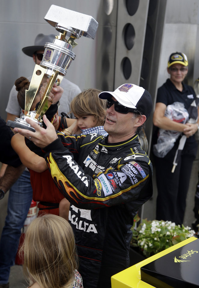 Photo - Jeff Gordon holds up the trophy after winning the NASCAR Brickyard 400 auto race at Indianapolis Motor Speedway in Indianapolis, Sunday, July 27, 2014.  (AP Photo/Darron Cummings)
