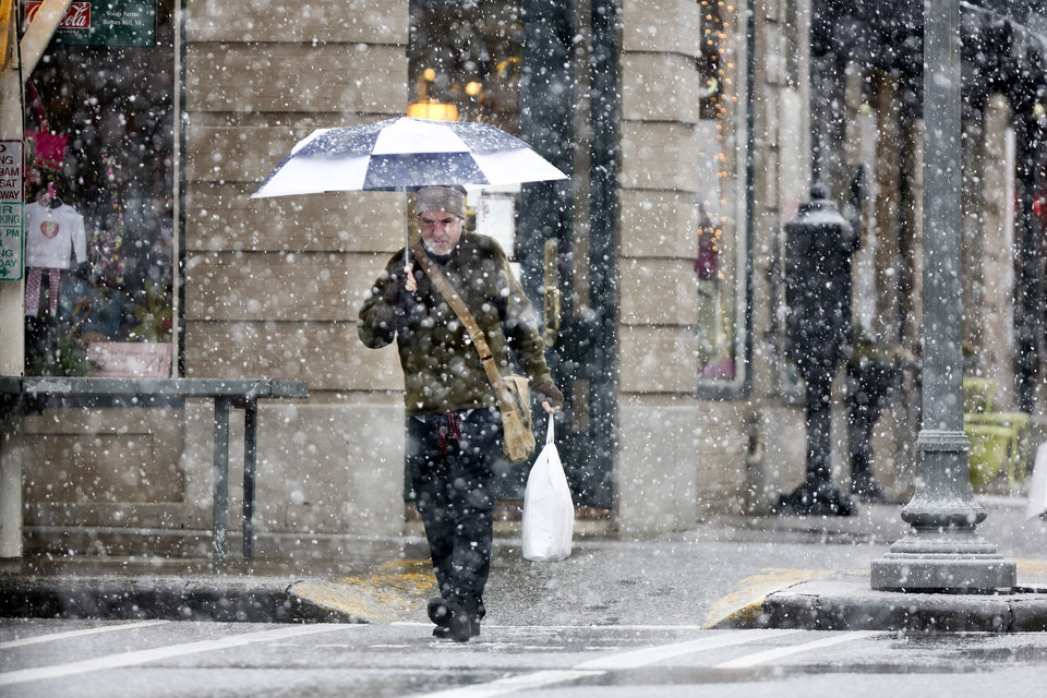 Photo - Christopher Manis uses an umbrella to protect himself from heavy snow falling in downtown Roanoke, Va., on Thursday afternoon Jan. 17, 2013.   Virginia is bracing for the first significant snowstorm of the winter season.   (AP PHOTO/The Roanoke Times, Kyle Green)   LOCAL TV OUT; SALEM TIMES REGISTER OUT; FINCASTLE HERALD OUT;  CHRISTIANBURG NEWS MESSENGER OUT; RADFORD NEWS JOURNAL OUT; ROANOKE STAR SENTINEL OUT