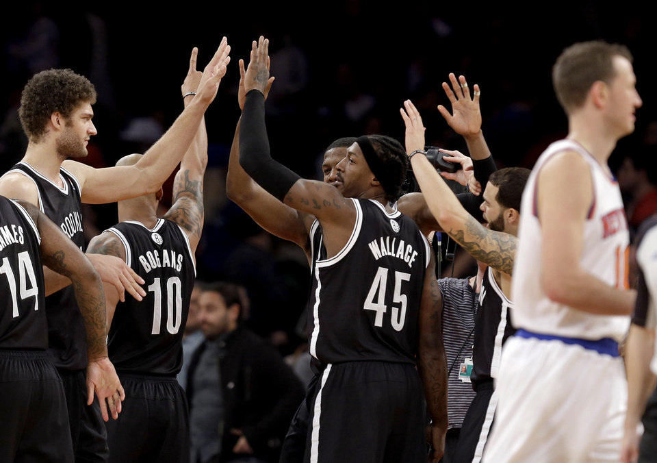 From left, Brooklyn Nets center Brook Lopez, guard Keith Bogans (10), guard Joe Johnson, forward Gerald Wallace (45) and guard Deron Williams celebrate their 88-85 win as New York Knicks forward Steve Novak, right, walks by, following their NBA basketball game at Madison Square Garden in New York, Monday, Jan. 21, 2013. (AP Photo/Kathy Willens)