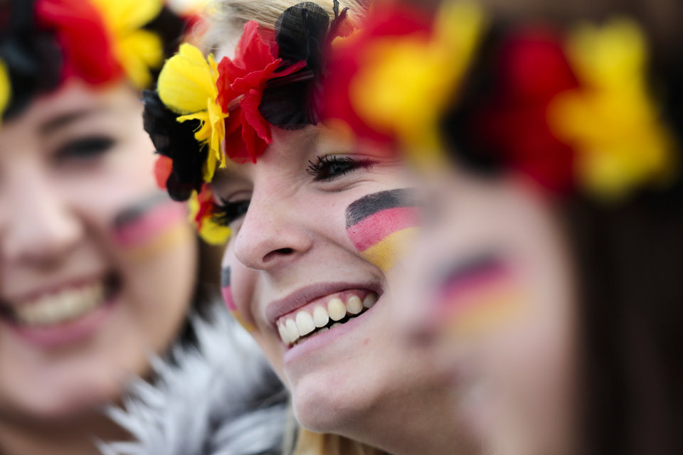 Photo - Three women arrive at the airport Tegel to welcome German national soccer team in Berlin Tuesday, July 15, 2014. Germany beat Argentina 1-0 on Sunday to win its fourth World Cup title.  (AP Photo/Markus Schreiber)