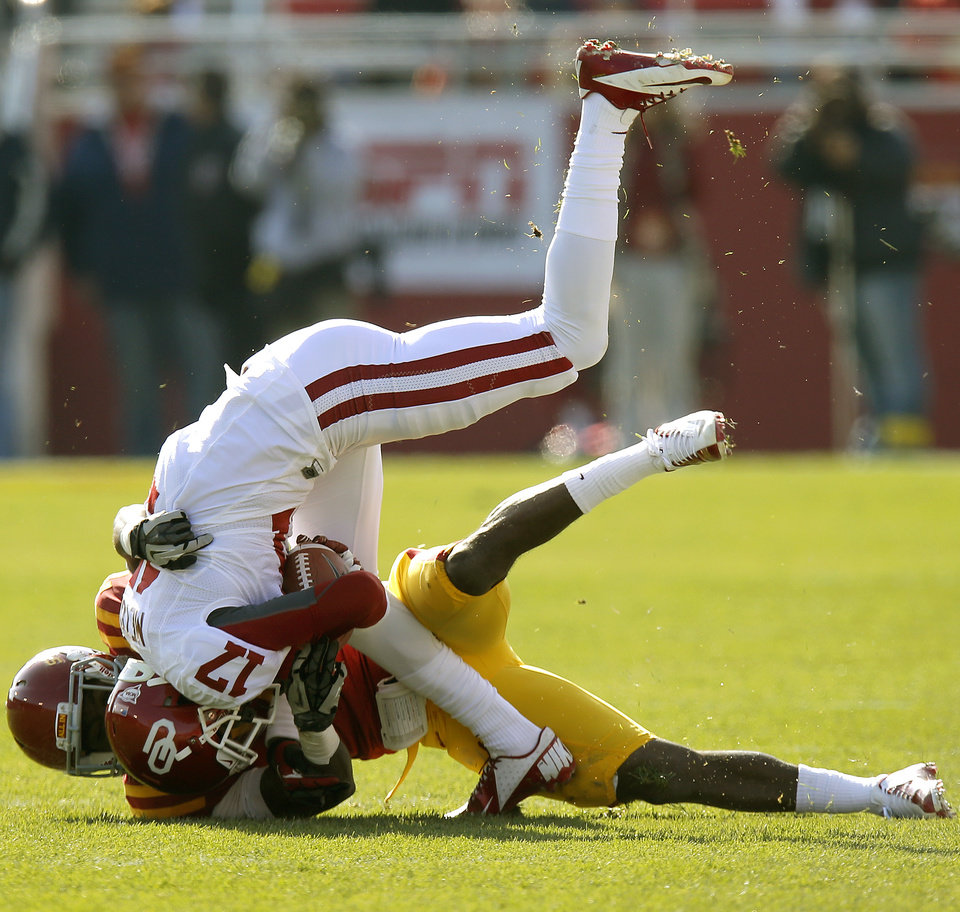 Photo - Oklahoma's Trey Metoyer (17) is brought down by Iowa State's Cliff Stokes (7) during a college football game between the University of Oklahoma (OU) and Iowa State University (ISU) at Jack Trice Stadium in Ames, Iowa, Saturday, Nov. 3, 2012. Photo by Bryan Terry, The Oklahoman