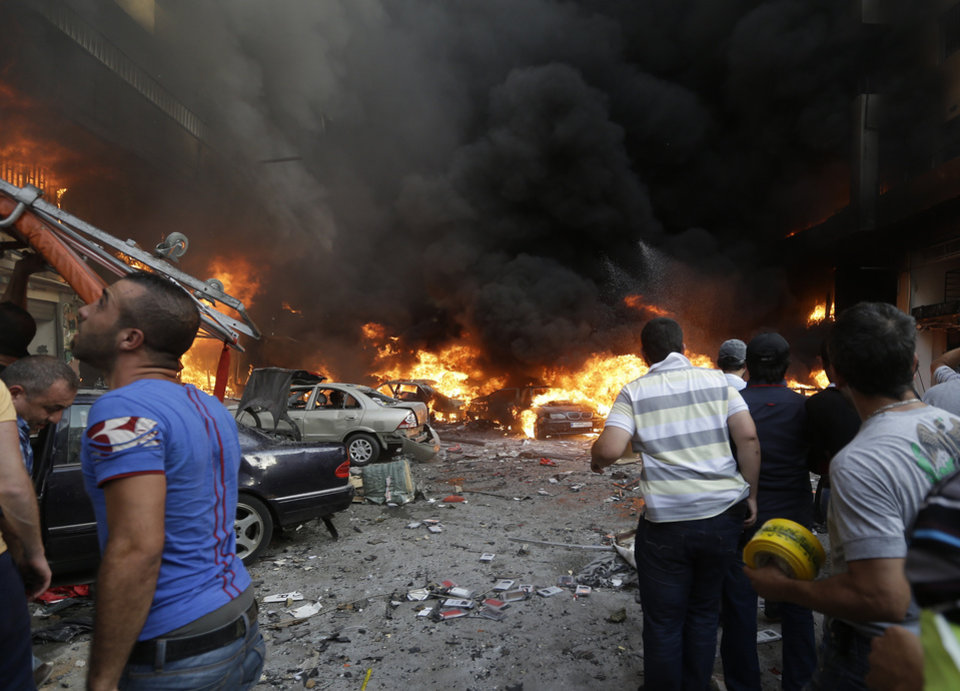 Photo - Lebanese citizens gather at the site of a car bomb explosion in southern Beirut, Lebanon, Thursday, Aug. 15, 2013. The powerful car bomb ripped through a southern Beirut neighborhood that is a stronghold of the militant group Hezbollah on Thursday, killing people and trapping others in burning buildings, the media said. (AP Photo/Hussein Malla)