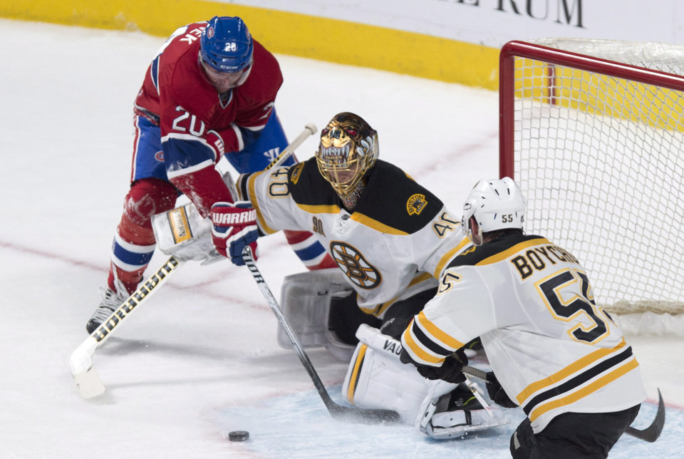 Photo - Boston Bruins goalie Tuukka Rask fends off Montreal Canadiens' Thomas Vanek as defenseman Johnny Boychuk looks on during second period NHL hockey action Wednesday, March 12, 2014 in Montreal. (AP Photo/The Canadian Press, Paul Chiasson)