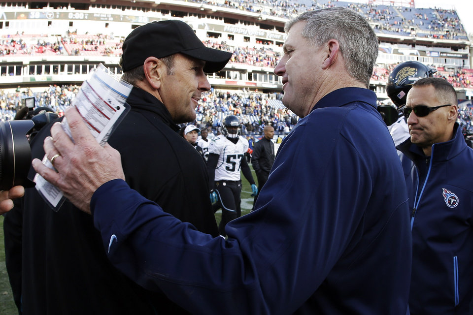 Photo - Tennessee Titans head coach Mike Munchak, right, and Jacksonville Jaguars head coach Mike Mularkey shake hands after an NFL football game, Sunday, Dec. 30, 2012, in Nashville, Tenn. The Titans won 38-20. (AP Photo/Wade Payne)