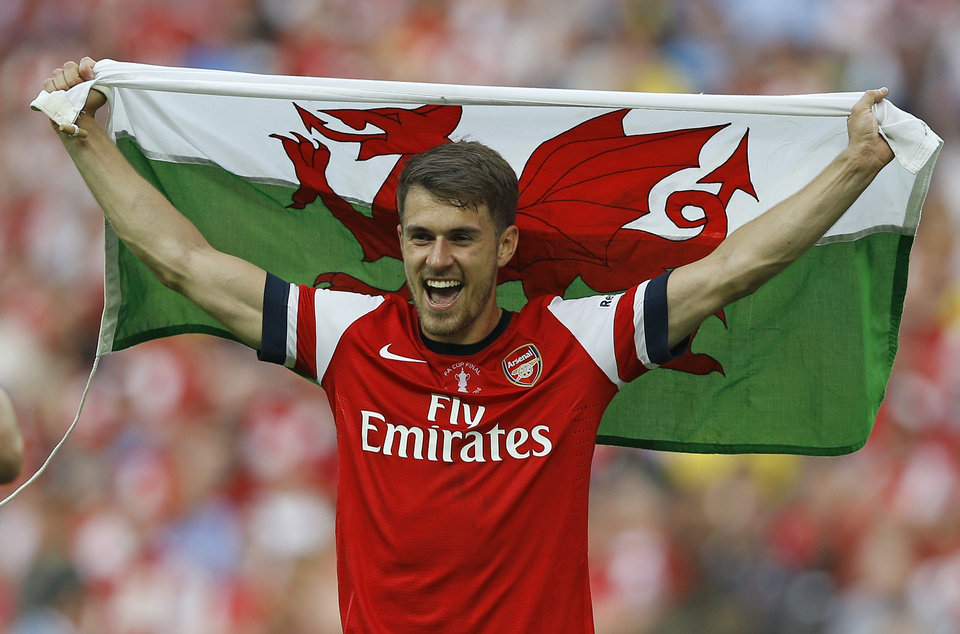 Photo - Arsenal's Aaron Ramsey celebrates holding the Welsh national flag after his team won the English FA Cup final soccer match between Arsenal and Hull City at Wembley Stadium in London, Saturday, May 17, 2014. Arsenal won 3-2 after extra-time. (AP Photo/Kirsty Wigglesworth)