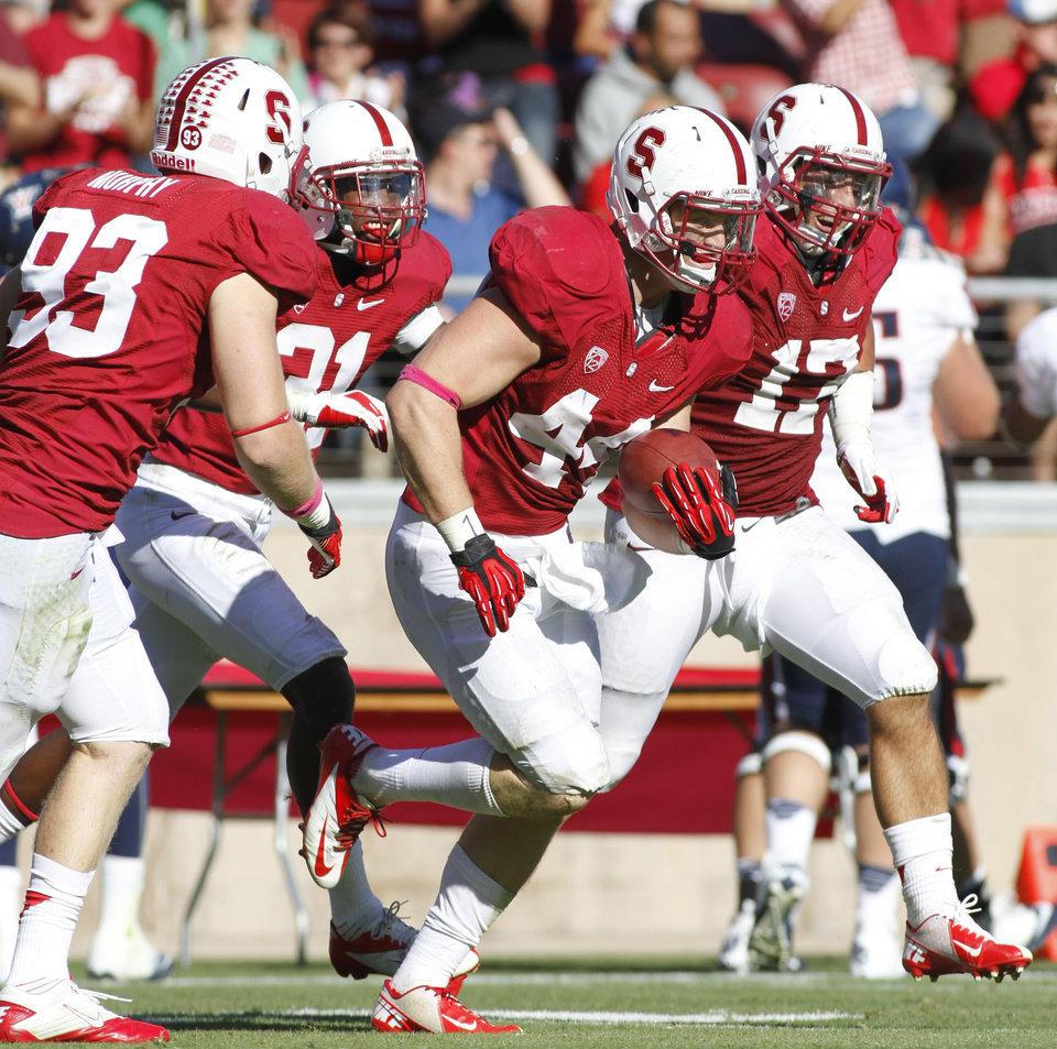 Photo -   Stanford'sChase Thomas, front with ball, celebrates with teammates, from left, Trent Murphy (93), Barry Browning and Kodi Whitfield after making an interception against Arizona in overtime during an NCAA college football game in Stanford, Calif., Saturday, Oct. 6, 2012. (AP Photo/George Nikitin)