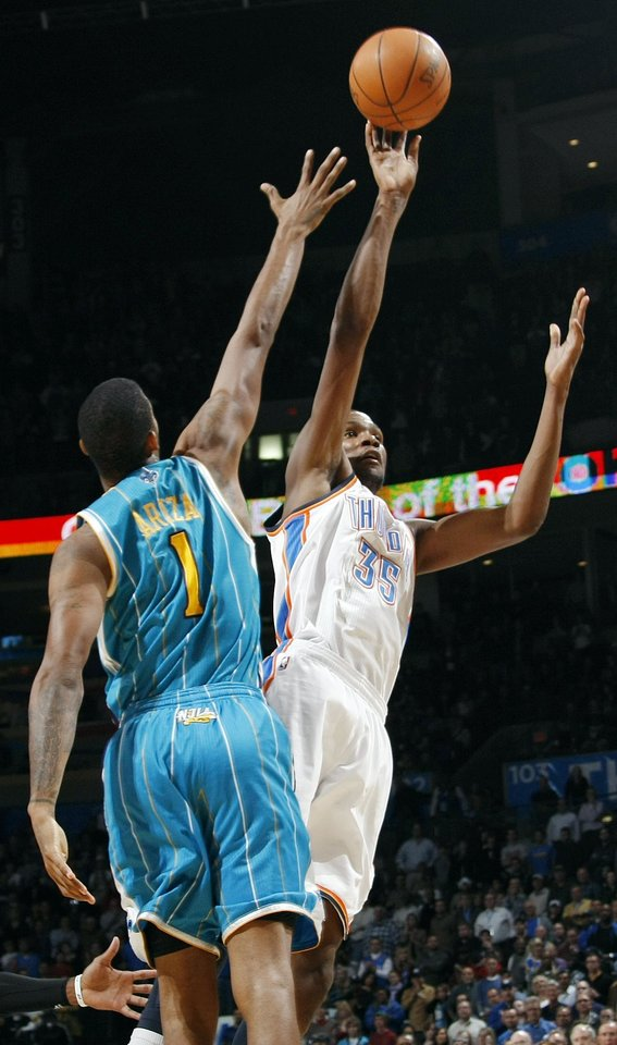 Photo - Oklahoma City's Kevin Durant (35) takes a shot past Trevor Ariza (1) of New Orleans during the NBA basketball game between the New Orleans Hornets and the Oklahoma City Thunder at the Oklahoma City Arena in downtown Oklahoma City, Monday, Nov. 29, 2010. Oklahoma City won, 95-89. Photo by Nate Billings, The Oklahoman