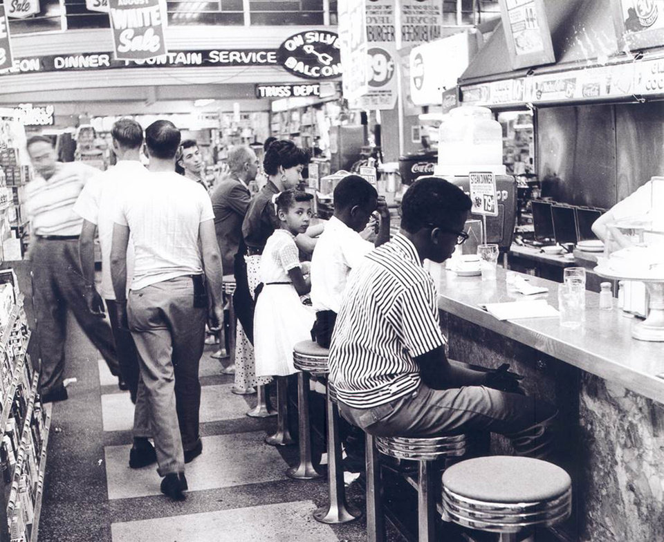 Photo -  Seven-year-old Ayanna Najuma, center, glances over her shoulder during a Aug. 19, 1958, sit-in at the Katz Drug Store lunch counter in downtown Oklahoma City. Children from the NAACP Youth Council took part in sit-ins in multiple businesses downtown beginning in 1958 to protest segregation. [Photo provided by the Oklahoma Historical Society]