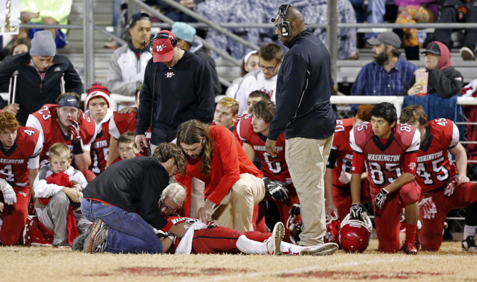 Photo - Washington player Brady Kulbeth is tended to after a second quarter injury as the Nowata Ironmen play the Washington Warriors in high school football on Friday, Nov. 28, 2014 in Washington, Okla. Photo by Steve Sisney, The Oklahoman