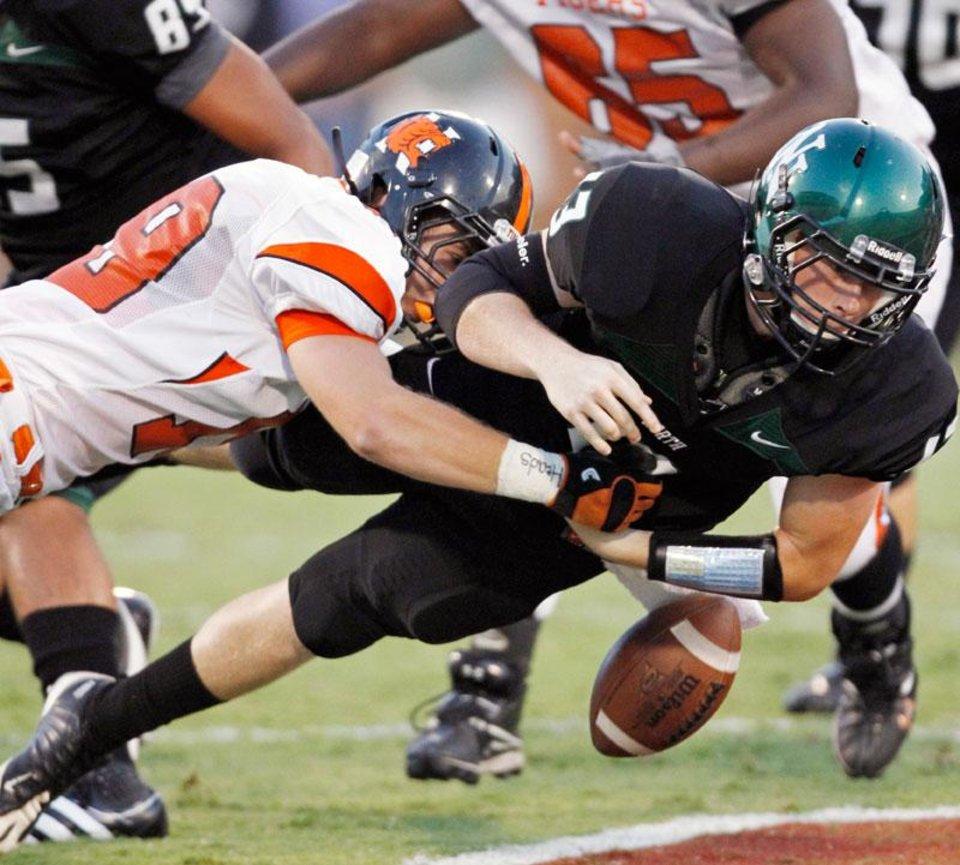 Photo -  Norman High's Michael Beard (19) knocks the ball from the hands of quarterback Peyton Gavras (13) in the first half as the Norman High School Tigers play the Norman North Timberwolves at Gaylord Family-Oklahoma Memorial Stadium on Thursday, Sept 1, 2011, in Norman, Okla.  The Tigers recovered the ball. Photo by Steve Sisney, The Oklahoman