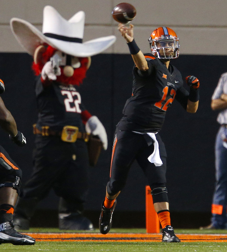 Photo - Oklahoma State's Daxx Garman (12) throws a pass during a college football game between the Oklahoma State Cowboys (OSU) and the Texas Tech Red Raiders at Boone Pickens Stadium in Stillwater, Okla., Thursday, Sept. 25, 2014. Photo by Bryan Terry, The Oklahoman