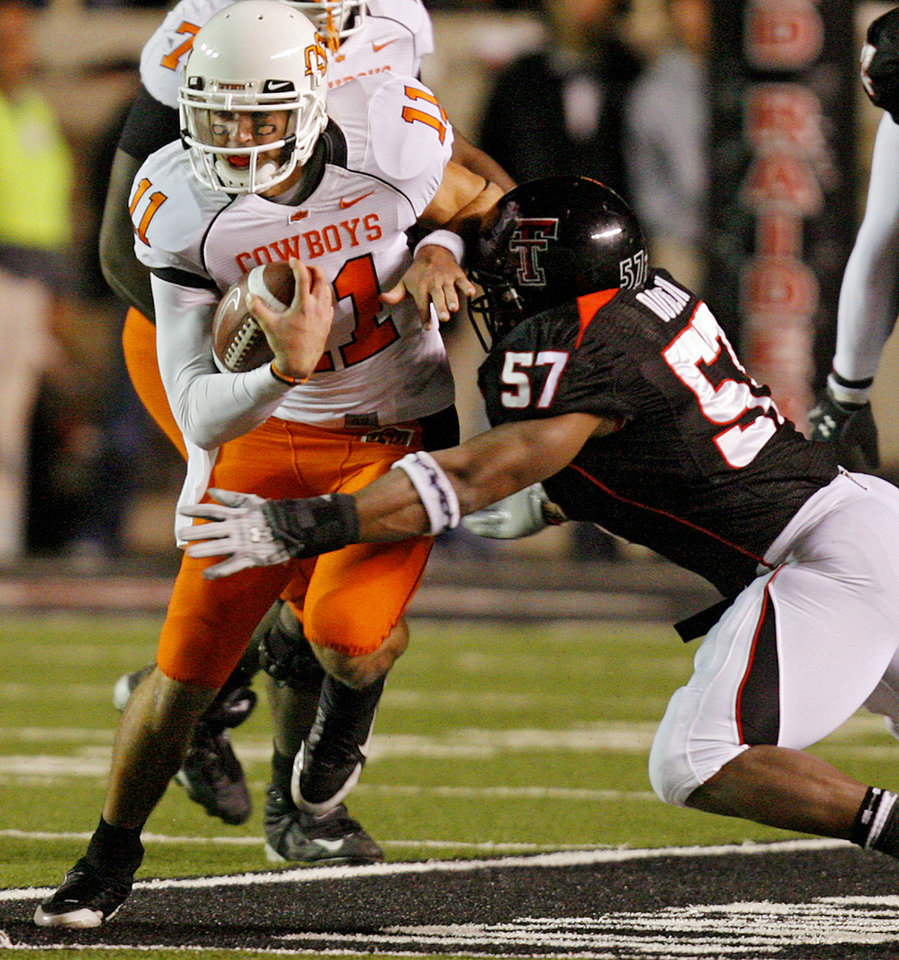 Photo - Oklahoma State's Zac Robinson (11) fights for more yardage against Texas Tech's Brian Duncan (57) during the first half of the college football game between the Oklahoma State University Cowboys (OSU) and the Texas Tech Red Raiders at Jones AT&T Stadium on Saturday, Nov. 8, 2008, in Lubbock, Tex.BY CHRIS LANDSBERGER/THE OKLAHOMAN