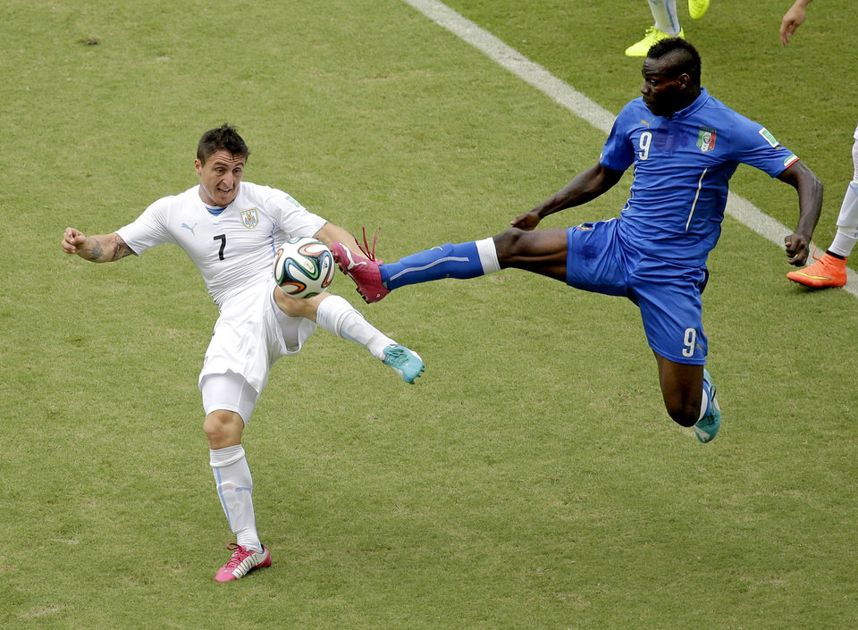 Photo - Italy's Mario Balotelli (9) and Uruguay's Cristian Rodriguez (7) battle for the ball during the group D World Cup soccer match between Italy and Uruguay at the Arena das Dunas in Natal, Brazil, Tuesday, June 24, 2014. (AP Photo/Hassan Ammar)