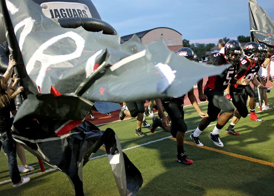 Photo - Westmoore Jaguars take the field before their game against Norman North at Moore's stadium in Moore, Okla., on Thursday, Sept. 16, 2010. Photo by John Clanton, The Oklahoman