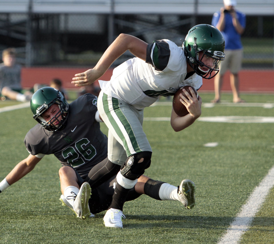 Photo - Edmond Santa Fe quarterback Keaton Torre is slowed by Norman North player Paxton Pennington and then sacked during a high school football scrimmage at Harve Collins Field in Norman, Okla., on Thursday, Aug. 21, 2014. Photo by Steve Sisney, The Oklahoman
