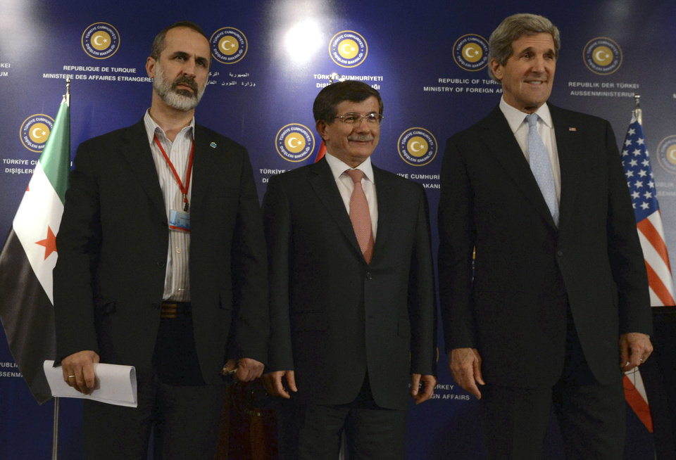 U.S. Secretary of State John Kerry, right, Turkish Foreign Minister Ahmet Davutoglu, center, and Syrian opposition leader Moaz al-Khatib pose for photos after a
