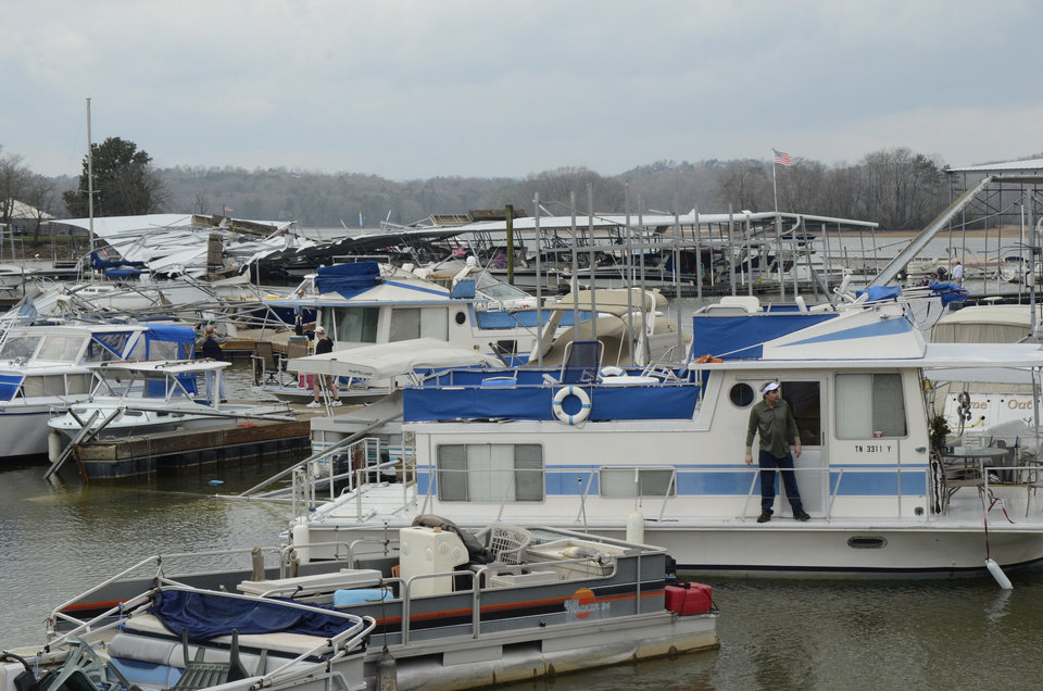 David Johnson checks out his houseboat at Island Cove Marina Friday, March 2, 2012 in Ooltewah, Tenn. Powerful storms stretching from the Gulf Coast to the Great Lakes flattened buildings in several states, wrecked two Indiana towns and bred anxiety across a wide swath of the country in the second powerful tornado outbreak this week. (AP Photo/Chattanooga Times Free Press, Angela Lewis) MANDATORY CREDIT ORG XMIT: TNCHA107