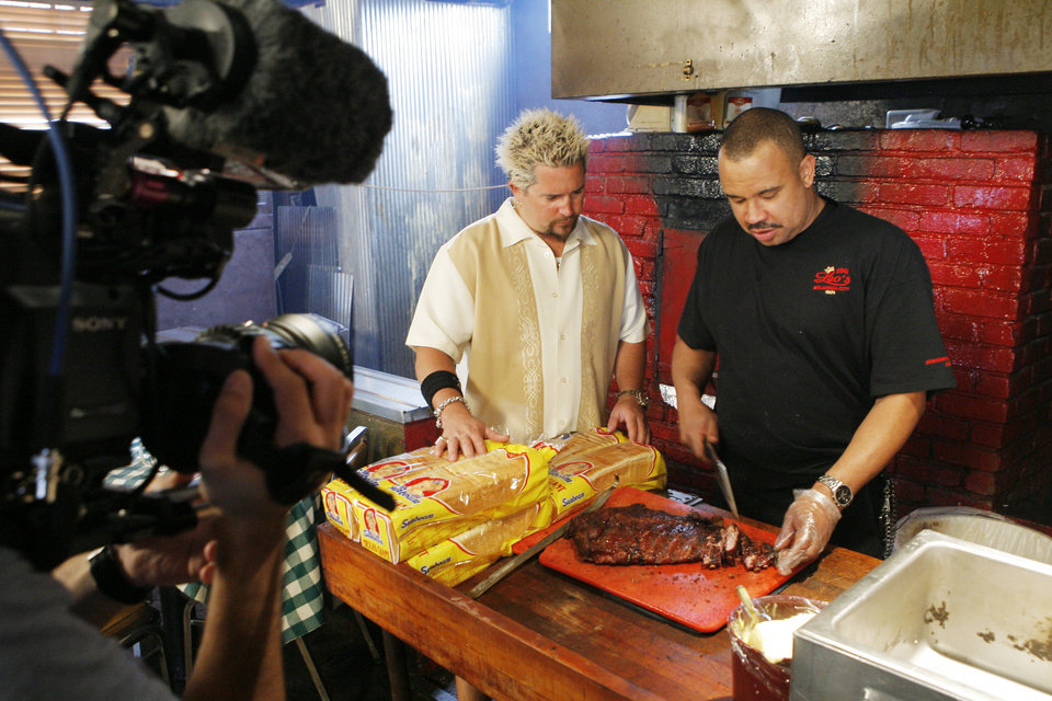 Photo - BARBECUE RESTAURANT: Food Network star Guy Fieri talks with Leo's BBQ owner Charles Smith during the filming of