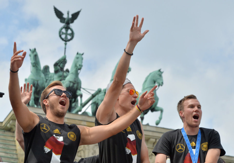 Photo - German  soccer players  Mario Goetze, left,  Julian Draxler ,center,  and  Kevin Großkreutz  celebrate in front of the Brandenburg Gate in Berlin, Tuesday July 15, 2014.  Germany's World Cup winners shared their fourth title with hundreds of thousands of fans by parading the trophy through cheering throngs to celebrate at the Brandenburg Gate on Tuesday. An estimated 400,000 people packed the