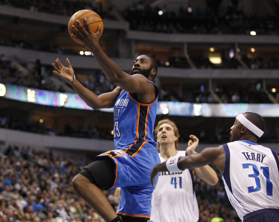 Photo - Oklahoma City Thunder guard James Harden (13) drives in front of Dallas Mavericks forward Dirk Nowitzki (41), of Germany, and guard Jason Terry (31) during the first half of an NBA basketball game Monday, Jan. 2, 2012, in Dallas. (AP Photo/Tim Sharp) ORG XMIT: DNA101
