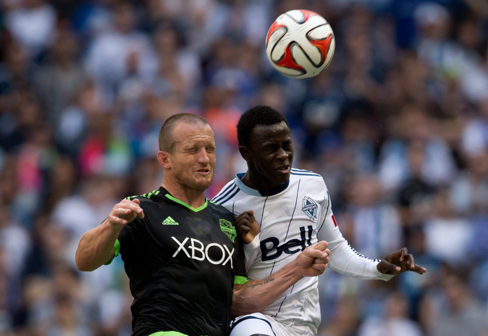 Photo - Seattle Sounders' Chad Barrett, left, and Vancouver Whitecaps' Kekuta Manneh, of Gambia, battle for the ball during the first half of an MLS soccer game in Vancouver, British Columbia, Saturday, May 24, 2014. (AP Photo/The Canadian Press, Darryl Dyck)