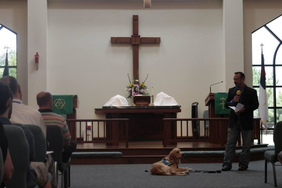Photo -  Koey Keylon, a member of St. Mark Lutheran Church in Edmond, with Rufus Comfort Dog, talks about the Lutheran Church Charities Comfort Dog Program at the Aug. 24 worship service. Photo by Mandy Long, for The Oklahoman