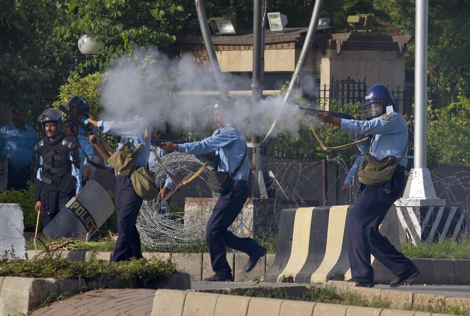 Pakistani police officers fire tear gas and rubber coated bullets toward protesters during clashes that erupted as the demonstrators tried to approach the U.S. embassy in Islamabad, Pakistan, Friday, Sept. 21, 2012. Protests by tens of thousands of Pakistanis infuriated by an anti-Islam film descended into deadly violence on Friday, with police firing tear gas and live ammunition in an attempt to subdue rioters who hurled rocks and set fire to buildings in some cities.  Four people were killed and dozens injured on a day the government declared a holiday to allow people to rally against the video. AP photo