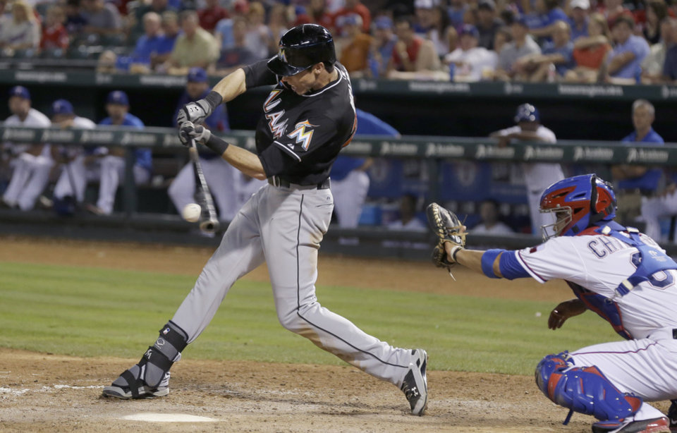 Photo - Miami Marlins Christian Yelich, left, hits a two run RBI single in front of Texas Rangers catcher Robinson Chirinos (61)  during the seventh inning of a baseball game in Arlington, Texas, Tuesday, June 10, 2014. Marlins Justin Bour and Jeff Mathis scored on the play.  (AP Photo/LM Otero)