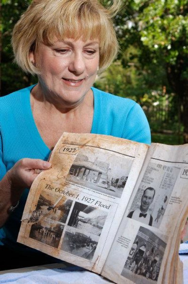 Sheila Rose found this wet and dirty book in her back yard Tuesday evening while cleaning up storm debris at her Midwest City home. The old book is about the early history of Chickasha. JIM BECKEL - THE OKLAHOMAN