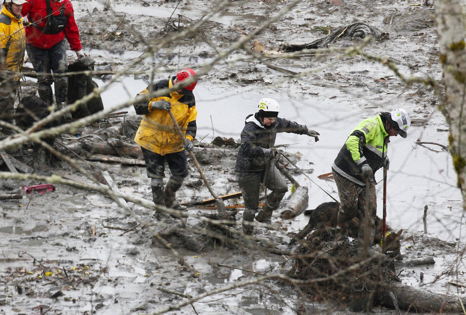 Photo - Search and rescue teams navigate the wet, muddy terrain at the west side of the mudslide on Highway 530 near mile marker 37 on Sunday, March 30, 2014, in Arlington, Wash. Periods of rain and wind have hampered efforts the past two days, with some rain showers continuing today. (AP Photo/Rick Wilking, Pool)