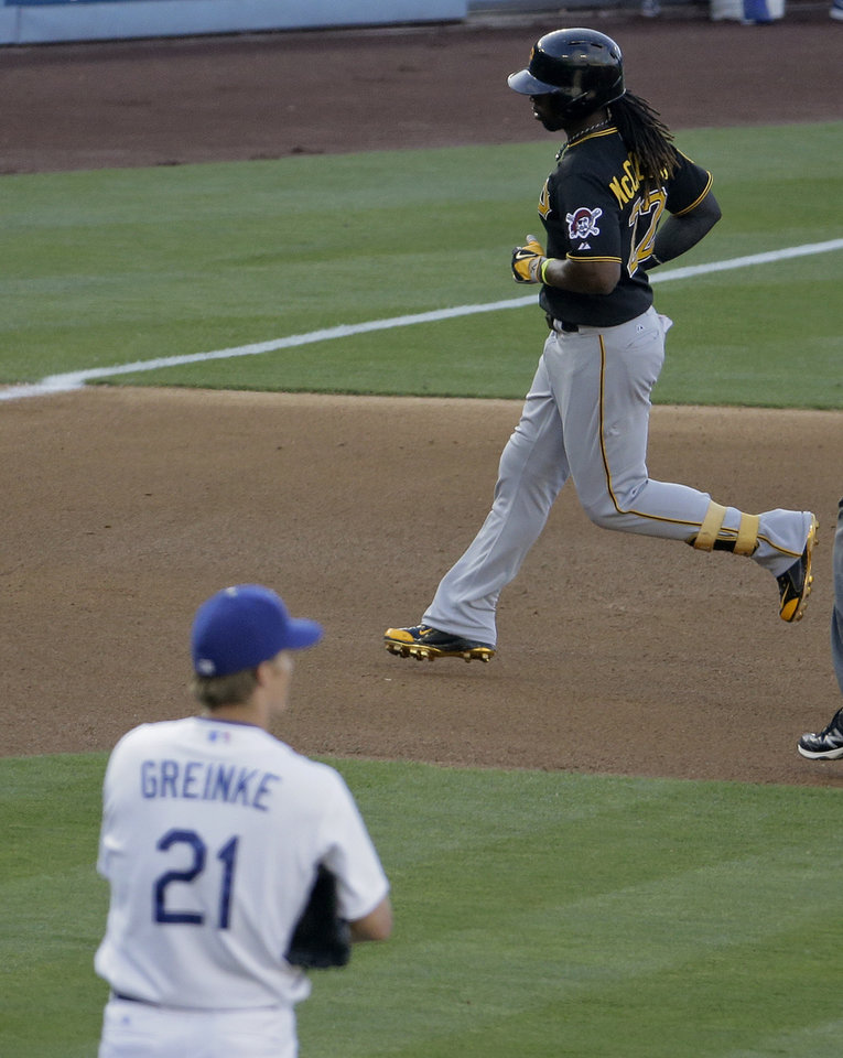 Pittsburgh Pirates' Andrew McCutchen, right, rounds the bases after his home run as Los Angeles Dodgers starting pitcher Zack Greinke looks on during third inning of a baseball in Los Angeles, Sunday, June 1, 2014. (AP Photo/Chris Carlson)