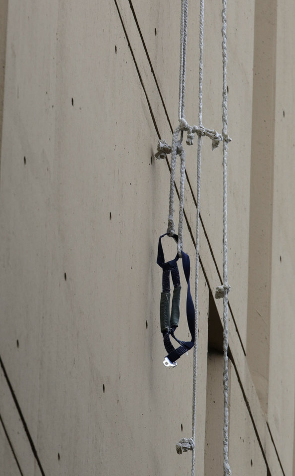 Photo - A harness and the end of a rope dangles from a window on the back side of the Metropolitan Correctional Center Tuesday, Dec. 18, 2012, in Chicago. Two convicted bank robbers used a knotted rope or bed sheets to escape from the federal prison window high above downtown Chicago early Tuesday, a week after one of them made a courtroom vow of retribution, to federal judge. The escape occurred sometime between 5 a.m. and 8:45 a.m. when the inmates were discovered missing, Chicago Police Sgt. Mark Lazarro said. Hours later, what appeared to be a rope, knotted at six-foot intervals, could be seen dangling into an alley from a window of the Metropolitan Correctional Center approximately 20 stories above the ground. (AP Photo/M. Spencer Green)
