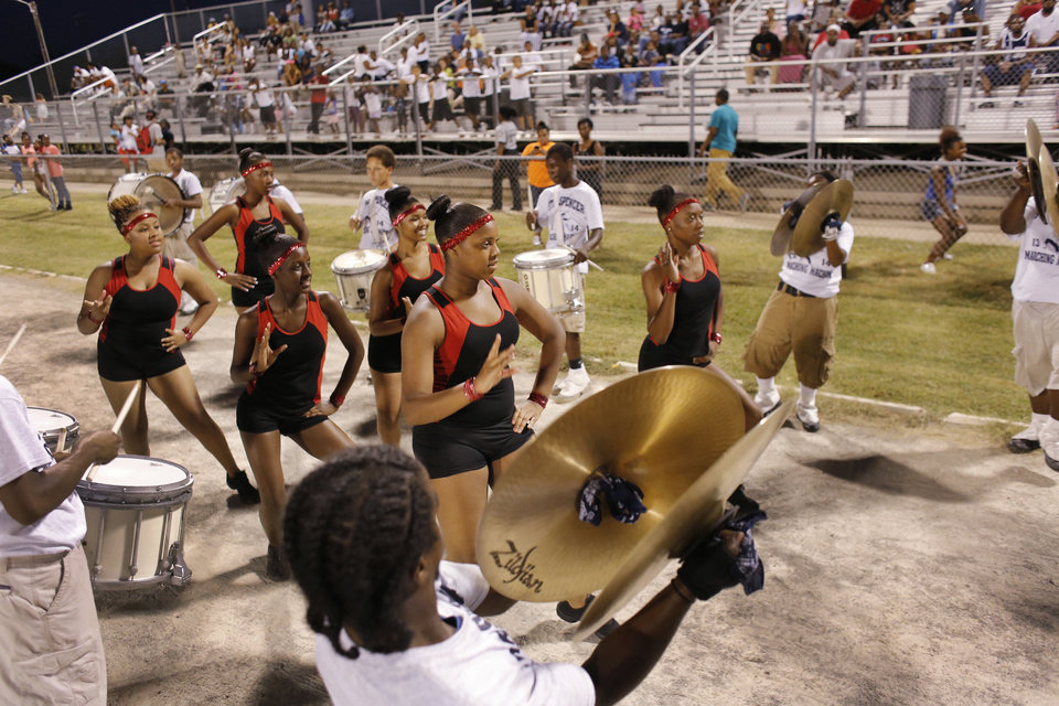Photo - The dance corp leave the field through a drum line after the halftime performance at the high school football game between Millwood and Star Spencer in Spencer, Thursday, September 5, 2013. Photo by Doug Hoke, The Oklahoman