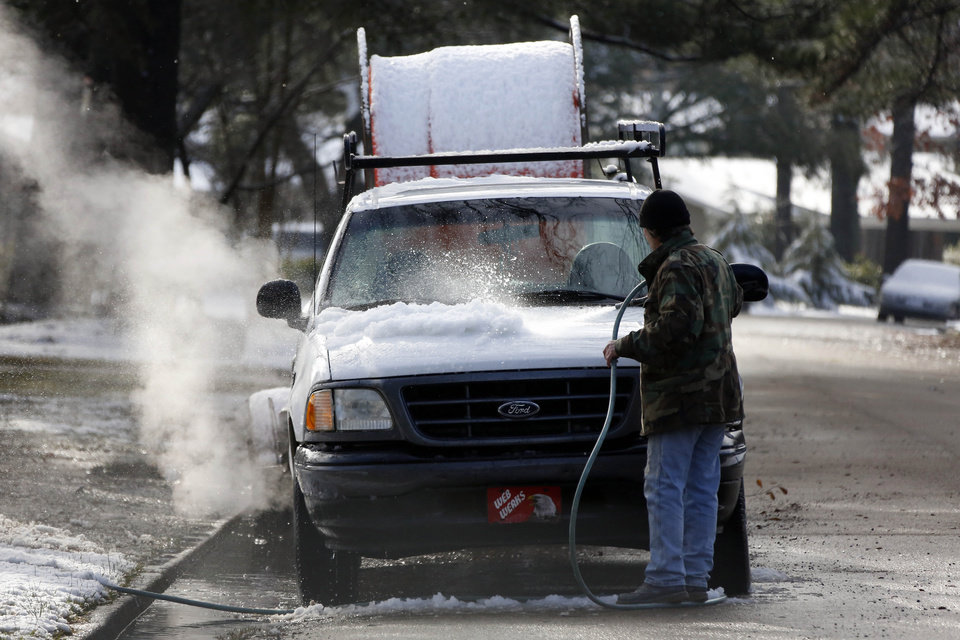 Photo - Mike Johnson, 60, washes off the snow from his service truck in Jackson, Miss., Thursday,  Jan. 17, 2013 following an early morning snowfall.  A winter storm system left 2 to 4 inches of snow in parts of central Mississippi before heading east toward Alabama, the National Weather Service said. (AP Photo/Rogelio V. Solis)