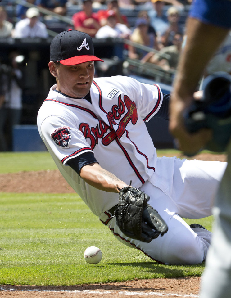 Photo - Atlanta Braves relief pitcher Luis Avilan (43) fields a bunt by Los Angeles Dodgers' Dee Gordon in the ninth of a baseball game Thursday, Aug. 14, 2014, in Atlanta. Gordon was safe at first and credited with a base hit. The Dodgers won 6-4. (AP Photo/John Bazemore)