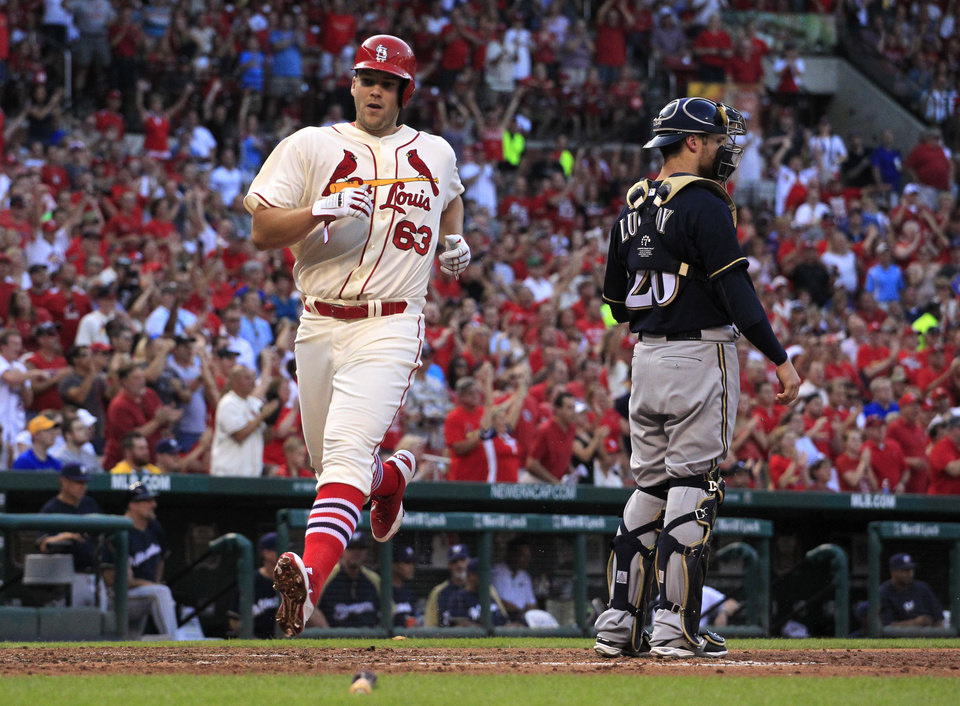 Photo - St. Louis Cardinals' Justin Masterson, left, scores past Milwaukee Brewers catcher Jonathan Lucroy on a two-run single by Kolten Wong during the second inning of a baseball game Saturday, Aug. 2, 2014, in St. Louis. (AP Photo/Jeff Roberson)