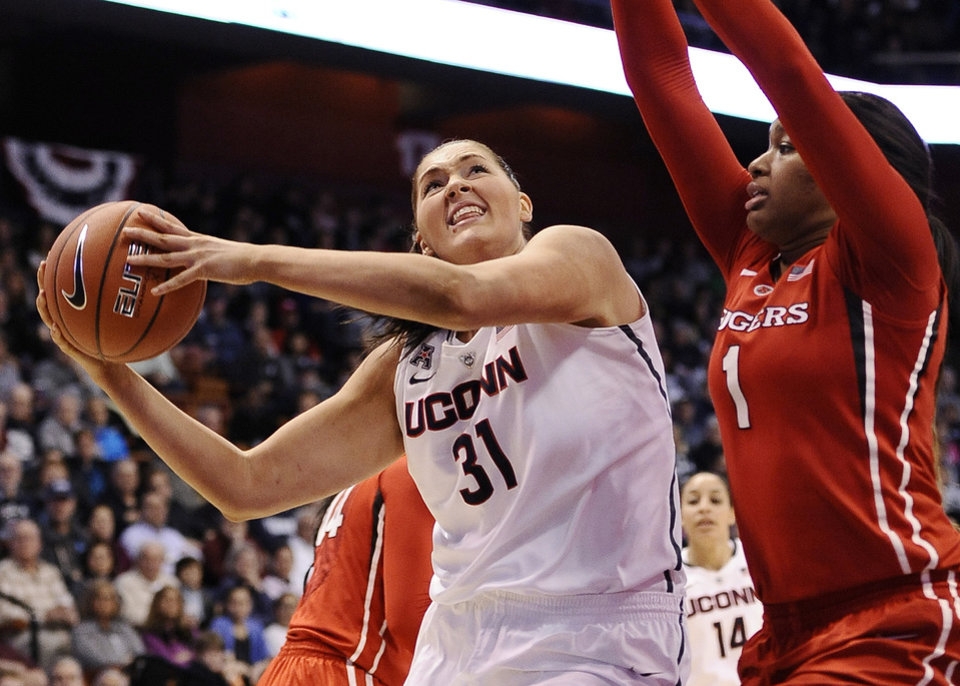 Photo - Connecticut's Stefanie Dolson (3) looks to shoot as Rutgers Rachel Hollivay, right, defends during the second half of an NCAA college basketball game in the semifinals of the American Athletic Conference women's tournament on Sunday, March 9, 2014, in Uncasville, Conn. Connecticut won 83-57. (AP Photo/Jessica Hill)