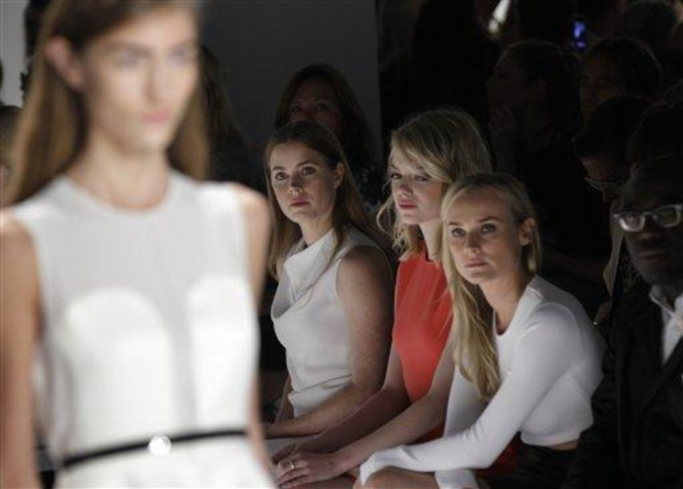 A model, far left, walks the runway wearing a design from the Calvin Klein Spring 2013 collection as actresses Amy Adams, Emma Stone and Diane Kruger watch at Fashion Week in New York, Thursday, Sept. 13, 2012.  (AP Photo/Kathy Willens)