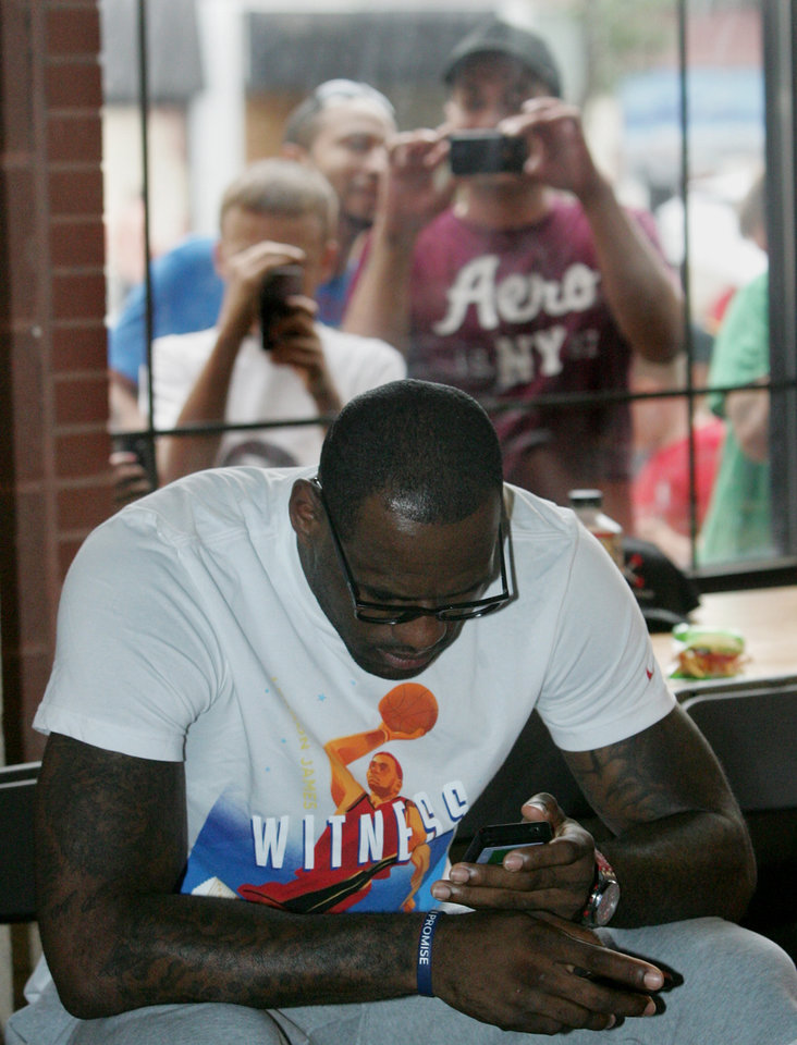 Photo -   ** ADDS MANDATORY CREDIT** Fans snap photos of NBA star and Akron native LeBron James as he waits for a press event during the LeBron James Family Foundation's Wheels for Education