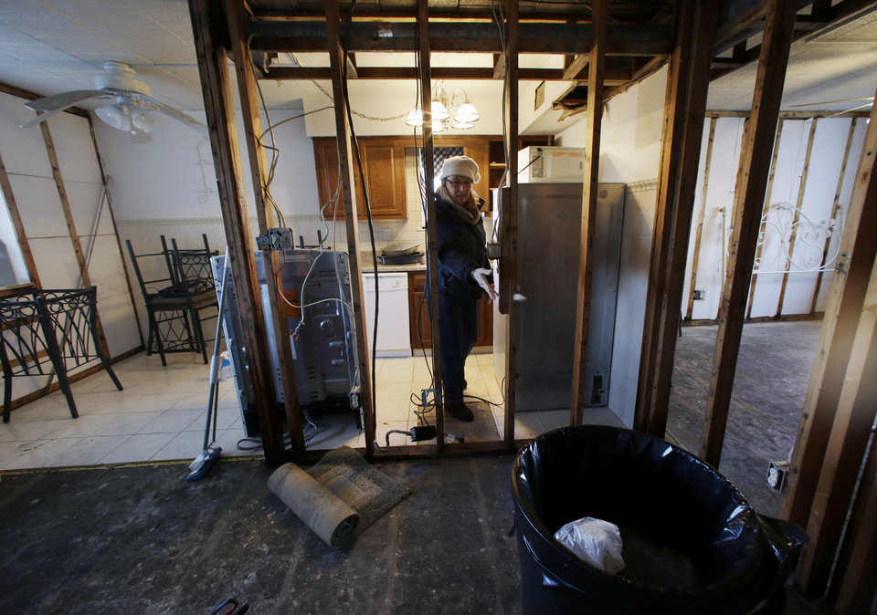 In rooms that have the walls stripped out, Kim Baker works to clean up her Superstorm Sandy  damaged home in Seaside Heights, N.J., Thursday, Jan. 3, 2013. New Jersey Gov. Chris Christie, a Republican who has praised President Barack Obama's handling of Superstorm Sandy, has blasted U.S. House Speaker John Boehner for delaying a vote for federal storm relief. Under intense pressure from angry Republicans, House Speaker John Boehner has agreed to a vote this week on aid for Superstorm Sandy recovery.  (AP Photo/Mel Evans)