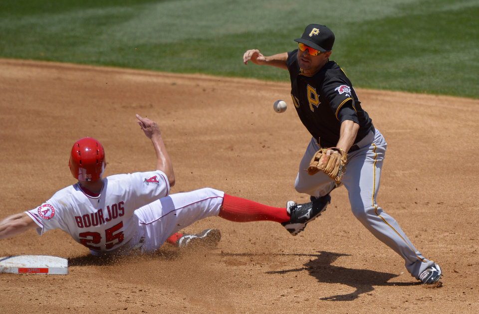 Photo - Los Angeles Angels' Peter Bourjos, left, is forced out at second, but breaks up Pittsburgh Pirates shortstop Jordy Mercer's double play attempt on a fielder's choice by Mike Trout and during the second inning of their baseball game, Sunday, June 23, 2013, in Anaheim, Calif.  (AP Photo/Mark J. Terrill)