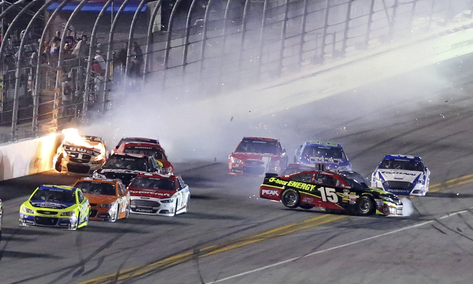 Photo - Flames come from Jimmie Johnson's car, left, as Clint Bowyer (15) spins while others try to avoid a crash during the second of two NASCAR Sprint Cup series qualifying auto races at Daytona International Speedway in Daytona Beach, Fla., Thursday, Feb. 20, 2014. (AP Photo/David Graham)
