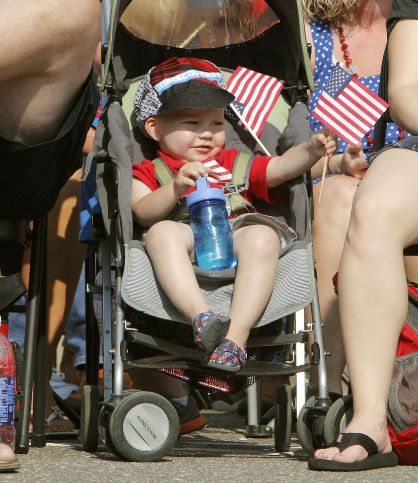 Photo - Two year old Cohen Copeland waves a flag during the annual LibertyFest Fourth of July Parade in downtown Edmond, OK, Thursday, July 4, 2013,  Photo by Paul Hellstern, The Oklahoman