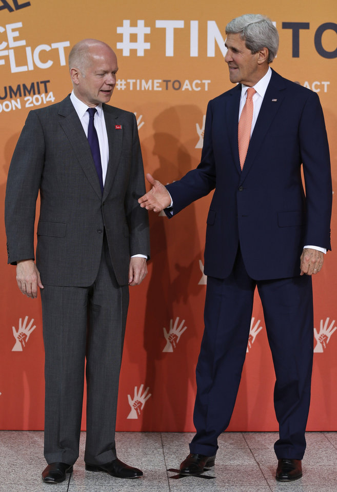 Photo - US Secretary of State John Kerry, right, and British Foreign Secretary William Hague, left, prepare to shake hands for the photographers at the 'End Sexual Violence in Conflict' summit in London, Friday, June 13, 2014. The Summit welcomed governments from over 100 countries, over 900 experts, NGOs, Faith leaders, and representatives from international organisations across the world. (AP Photo/Lefteris Pitarakis)
