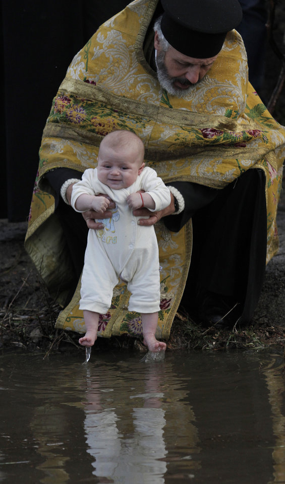 Photo - An Orthodox priest baptizes newborn baby in the icy waters of river Tundzha during celebrations of Epiphany day in the town of Kalofer, Bulgaria, Sunday, Jan. 6, 2013. Traditionally, an Eastern Orthodox priest throws a cross in the river and it is believed that the one who retrieves it will be healthy through the year. (AP Photo/Valentina Petrova)