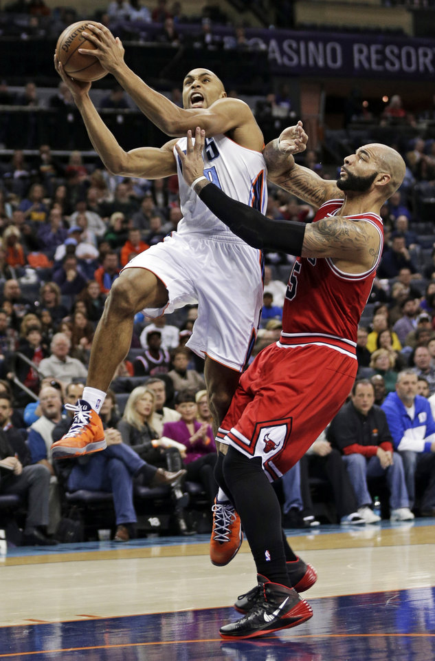 Photo - Charlotte Bobcats' Gerald Henderson, left, drives past Chicago Bulls' Carlos Boozer, right, during the first half of an NBA basketball game in Charlotte, N.C., Saturday, Jan. 25, 2014. (AP Photo/Chuck Burton)