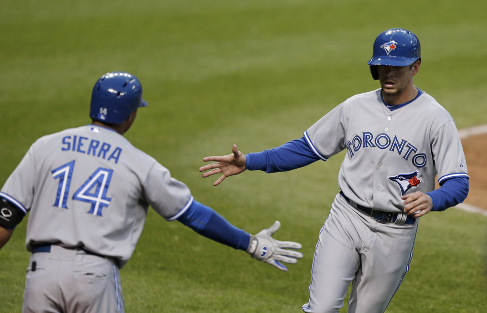 Photo - Toronto Blue Jays' Colby Rasmus, right, is congratulated by Moises Sierra after Rasmus scored on an RBI single by Brett Lawrie during the fourth inning of a baseball game against the Cleveland Indians, Friday, April 18, 2014, in Cleveland. (AP Photo/Tony Dejak)