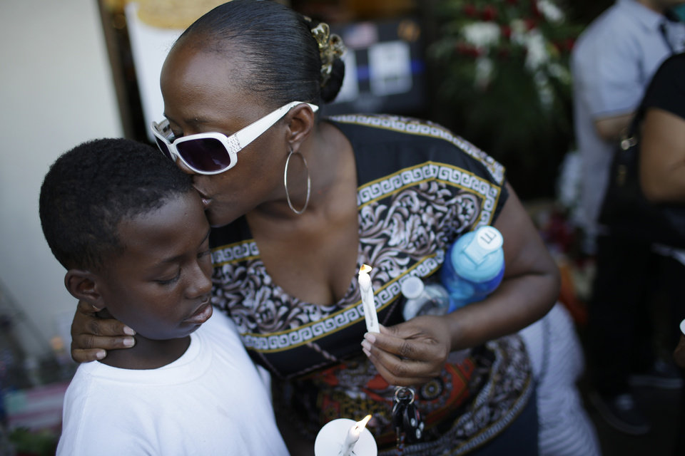 Photo - Tiffany Moore kisses her son Elijah Unce, 10, during a vigil at a CiCi's Pizza Monday, June 9, 2014 in Las Vegas. The vigil was held to honor two Las Vegas Metropolitan Police officers and a bystander who were killed Sunday. (AP Photo/John Locher)